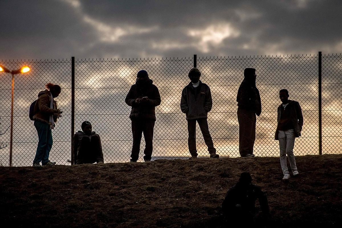 Refugeesbehind a fence at the Hungarian border with Serbia near the town of Horgos in September last year. The country is further fortifying its barriers to keep migrants out. Migrants standing against a fence in Coquelles near Calais where Britain h