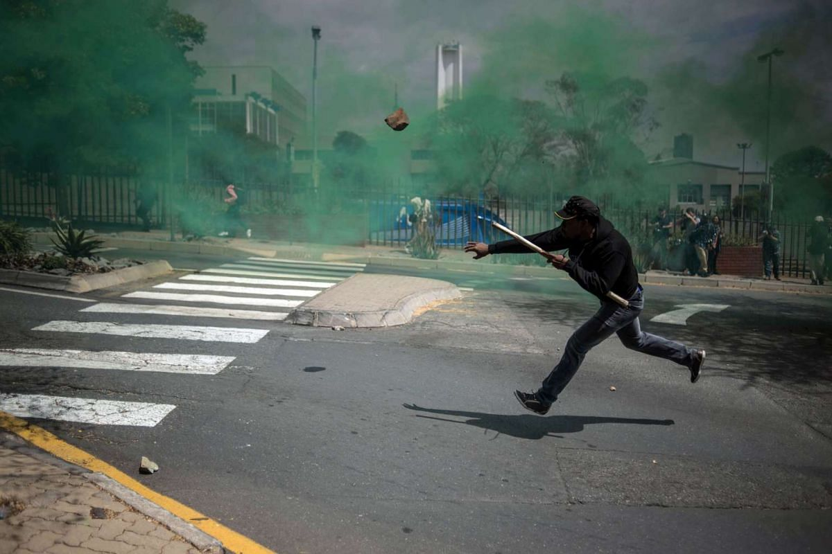 A man throws a stone during a mass protest of the Fees Must Fall movement at the University of Witwatersrand in Johannesburg on October 4, 2016. The university, along with many campuses across South Africa, has been closed for at least two weeks duri
