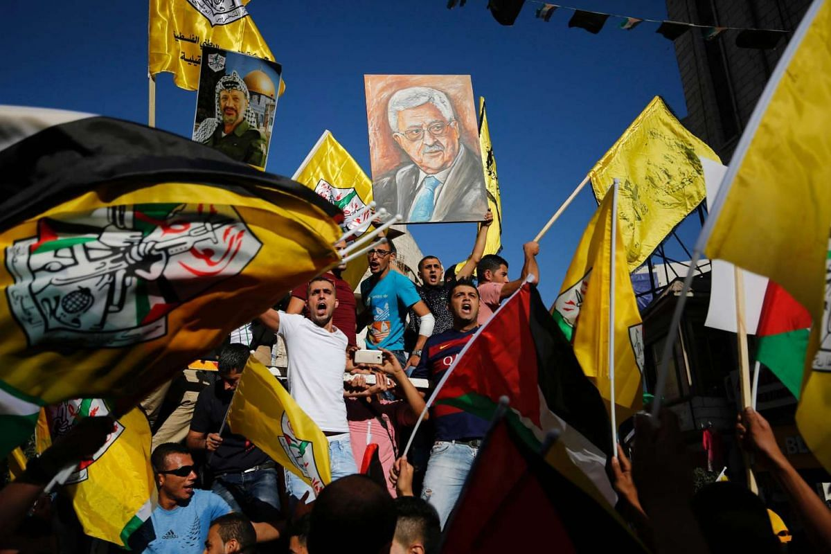 Palestinians supporting the Fatah movement wave both their national and the movement's flags as they take part in a demonstration in the West Bank city of Ramallah on October 4, 2016 in support of president Mahmud Abbas' (portrait) participation in t