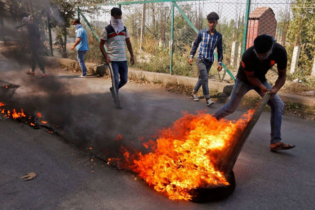 A masked demonstrator pulls a burning tyre during a protest in Srinagar, October 4, 2016. PHOTO: REUTERS