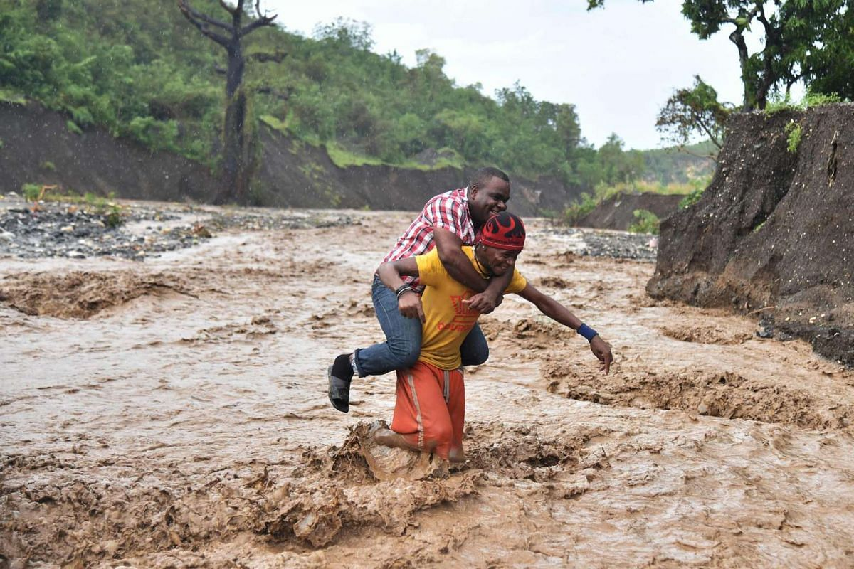 A man is carried across the river La Digue in Petit Goave, south-west of Port-au-Prince, where a bridge collapsed after Hurricane Matthew struck on Oct 5, 2016.