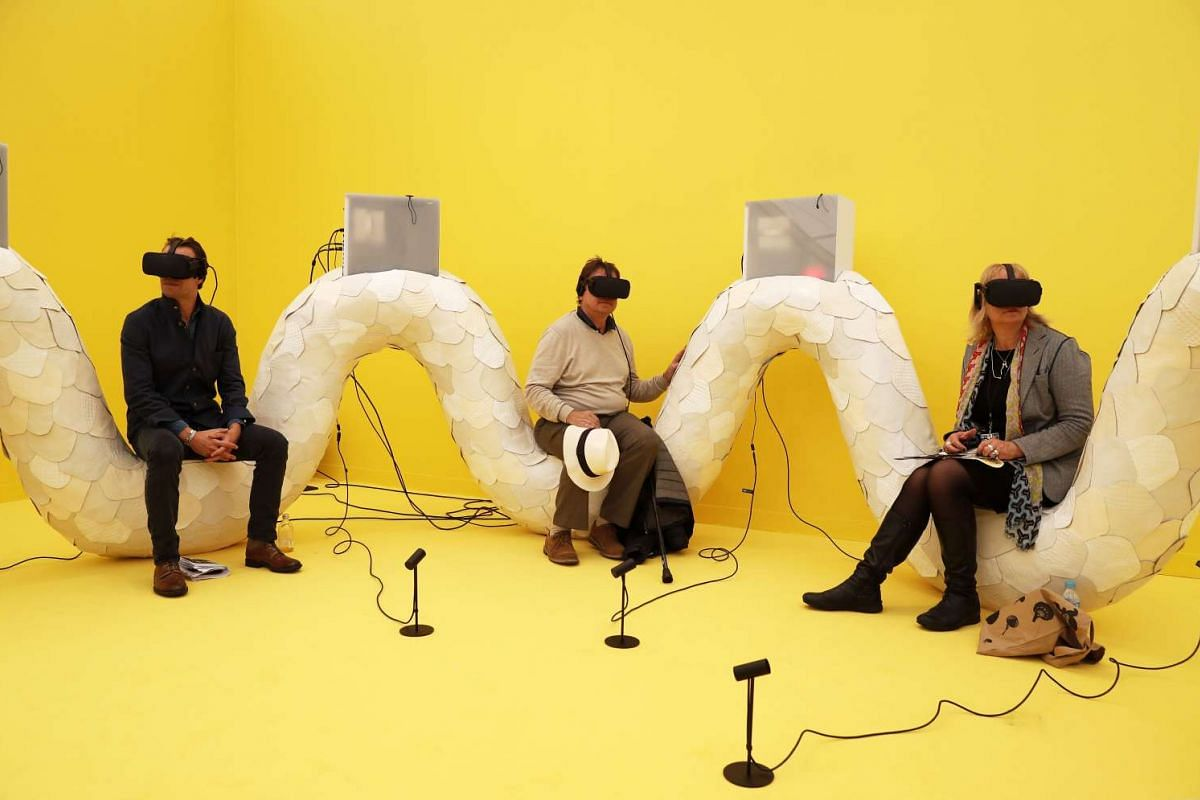 Visitors sit on an interactive art piece by Canadian Jon Rafman entitled Trans Dimensional Serpent, at the Frieze Art Fair in London on Oct 5, 2016.