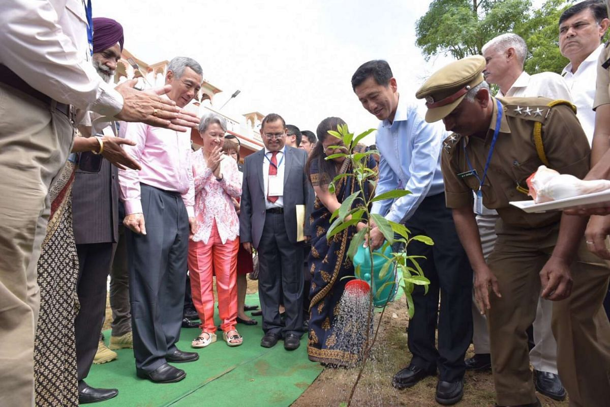 Prime Minister Lee Hsien Loong look on as Chief minister of Rajasthan Vasundhara Raje (centre) and Mr Ong Ye Kung plant a tree at the Centre of Excellence for Tourism Training (background) in Udaipur.
