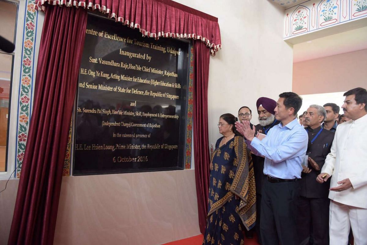 Chief minister of Rajasthan Vasundhara Raje (in sari) and Mr Ong Ye Kung unveil the Centre of Excellence for Tourism Training (background) in Udaipur.