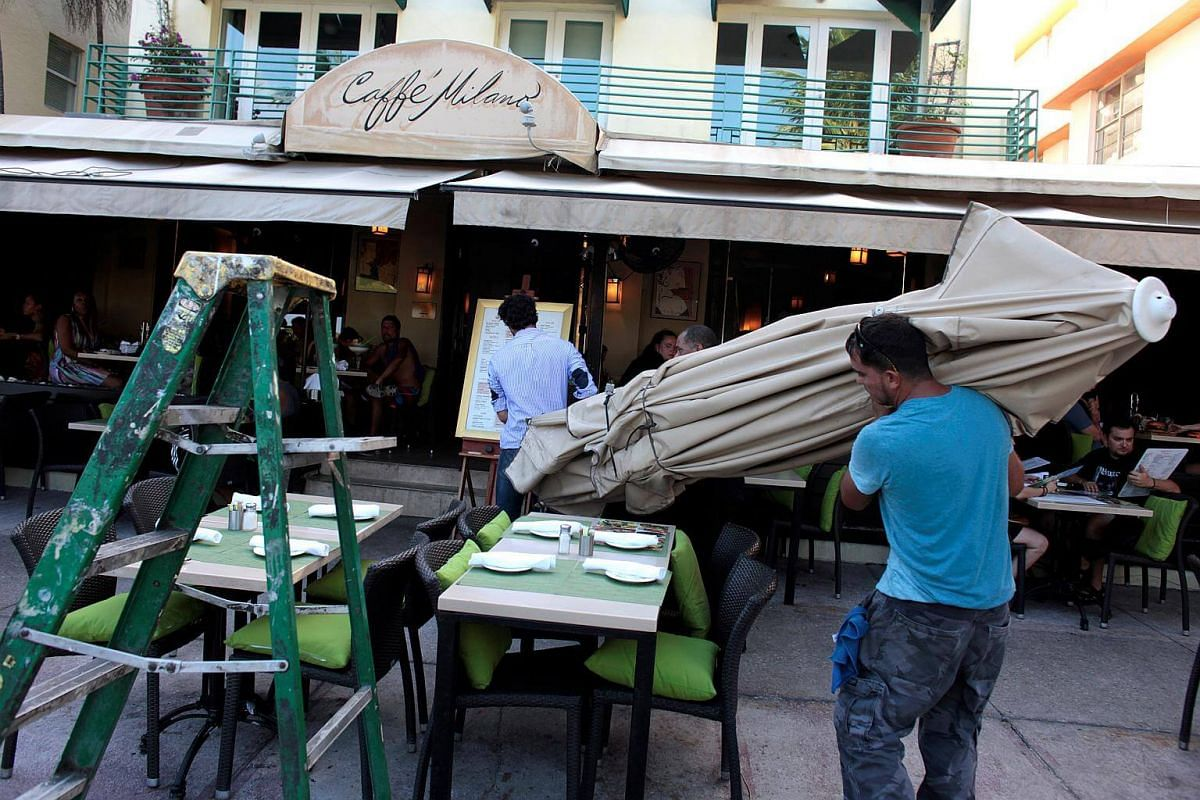 Workers remove umbrellas at Caffe Milano in anticipation of Hurricane Matthew in South Beach, Florida on Oct 5, 2016.