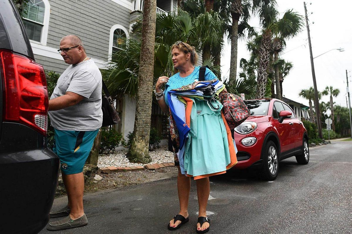 Ms Bridget DeHart removing some of her belongings as she and her husband Andrew Dehart leave their boarded up apartment ahead of Hurricane Matthew in Atlantic Beach, Florida, on Oct 5, 2016.