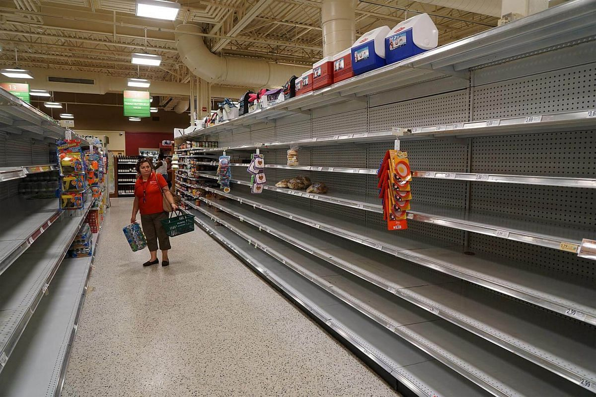 Customers browse empty shelves at a Publix Super Markets store ahead of Hurricane Matthew in West Palm Beach, Florida, on Oct 5, 2016.