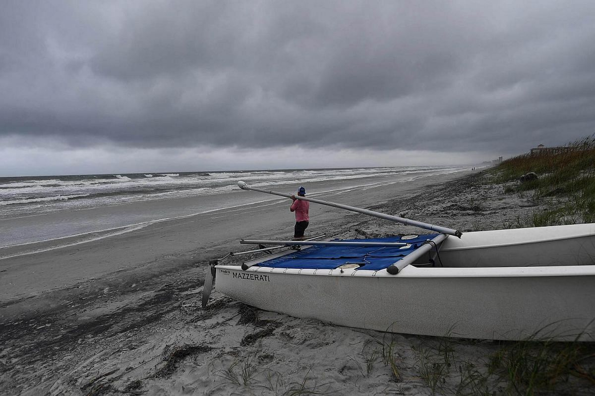 A man removes parts of his sailing boat from a beach in Florida's Atlantic Beach on Oct 5, 2016 before Hurricane Matthew strikes.