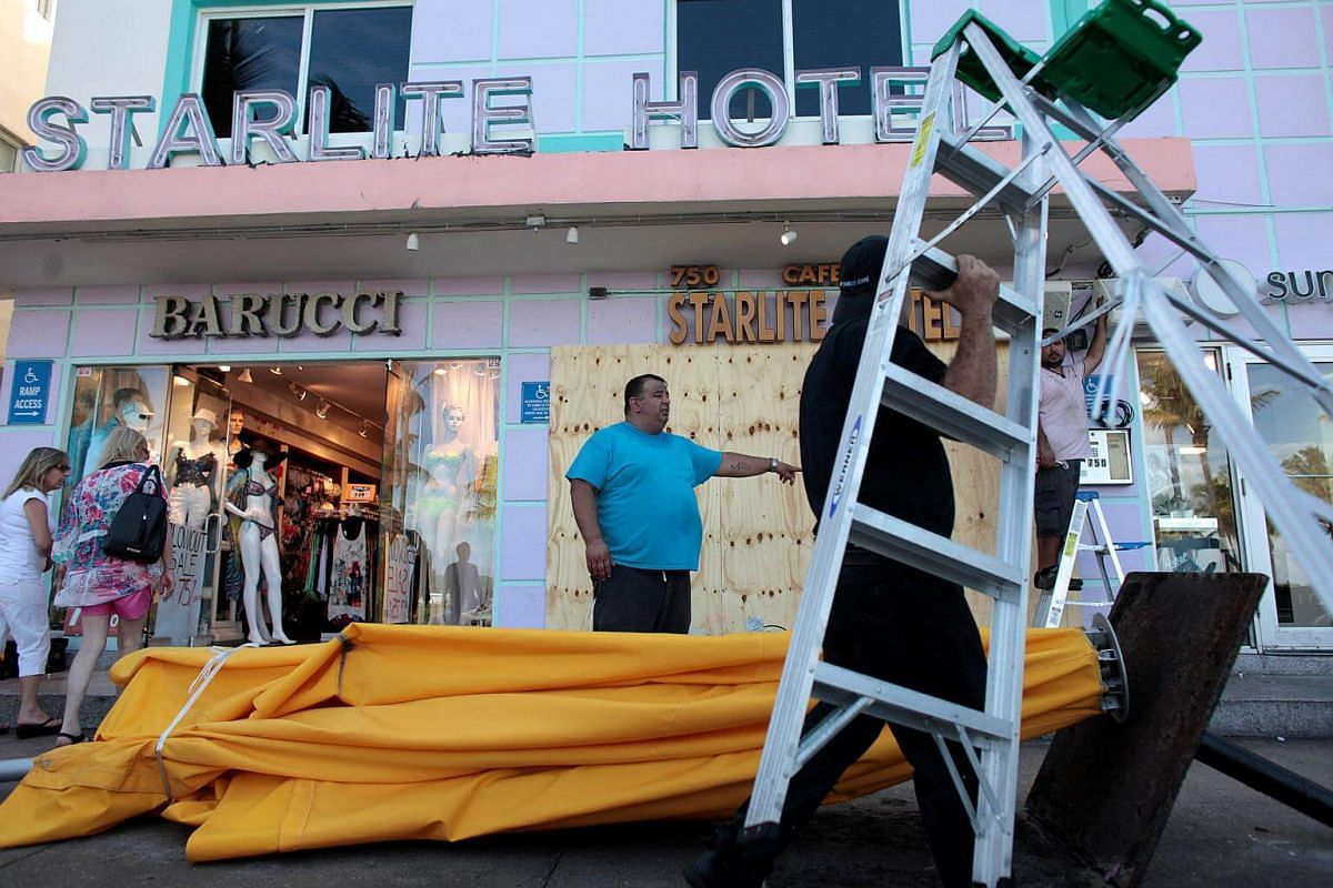 Workers remove umbrellas at the Starlite Hotel in anticipation of Hurricane Matthew in South Beach, Florida on Oct 5, 2016.