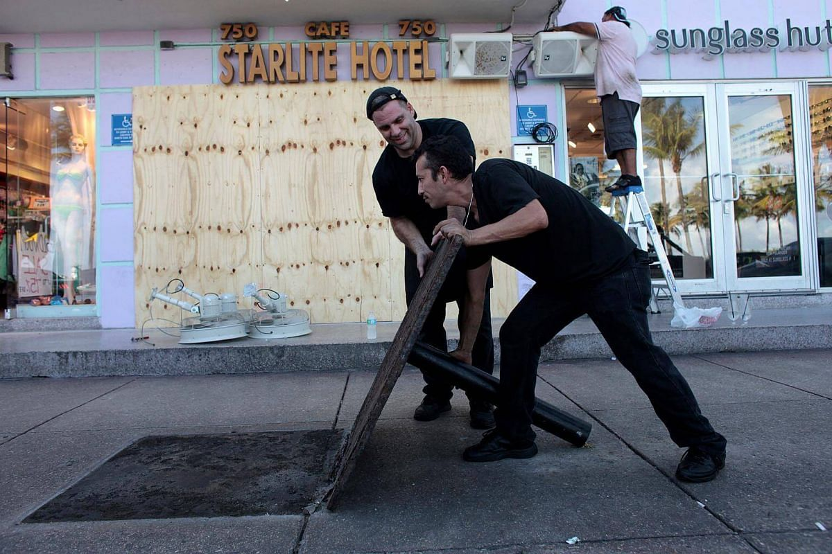 Workers remove the base of an umbrella at the Starlite Hotel in anticipation of Hurricane Matthew in South Beach, Florida on Oct 5, 2016.