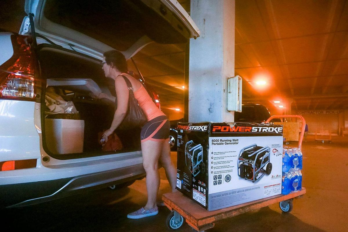 South Florida resident Andrea Kmetz buys a portable generator and bottled water in preparation for Hurricane Matthew in Fort Lauderdale on Oct 5, 2016.
