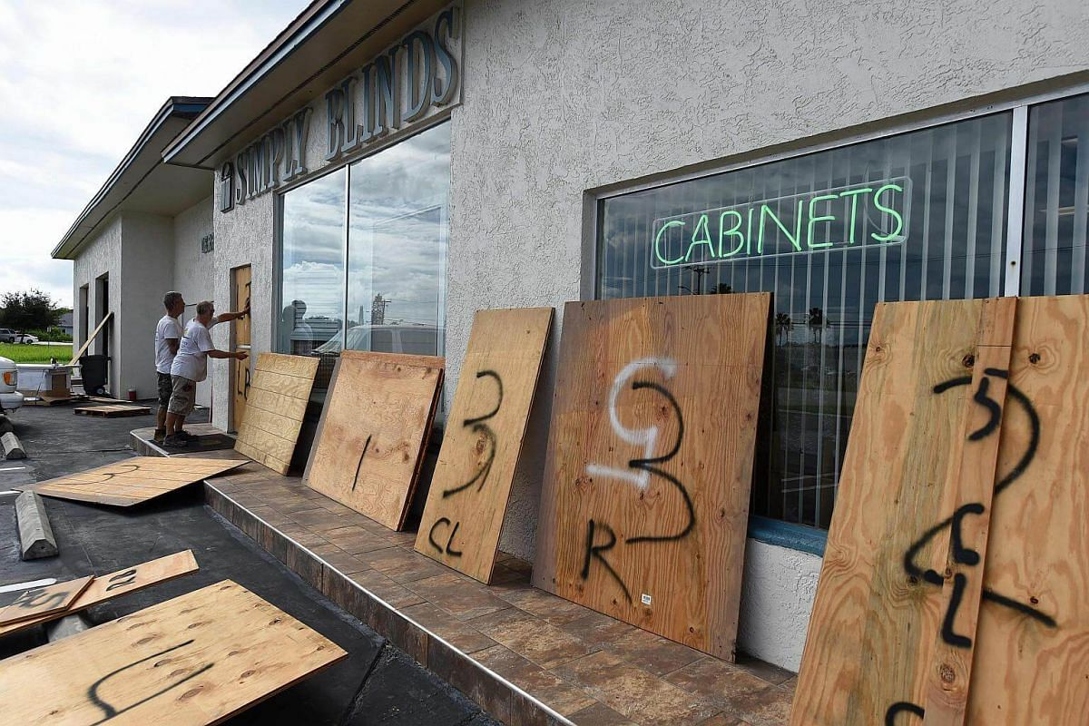 Mr Anthony Schirado (left) and Mr Tom Kennedy (right) put up plywood to protect the windows of a store ahead of Hurricane Matthew on Cocoa Beach, Florida on Oct 5, 2016.
