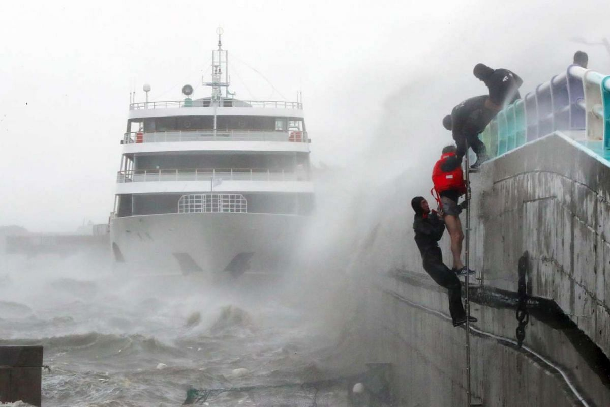 South Korean coast guards try to rescue crew members of a stranded passenger ship in the aftermath of Typhoon Chaba in the southern city of Yeosu on Oct 5, 2016.