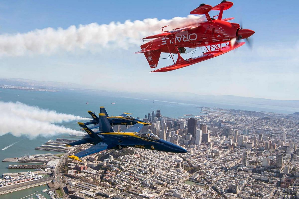 The US Navy Blue Angels numbers 5 and 6 fly below Sean Tucker (above) as he pilots the Oracle Challenger III over San Francisco, California as part of a practice run for Fleet Week on October 6, 2016. PHOTO: AFP