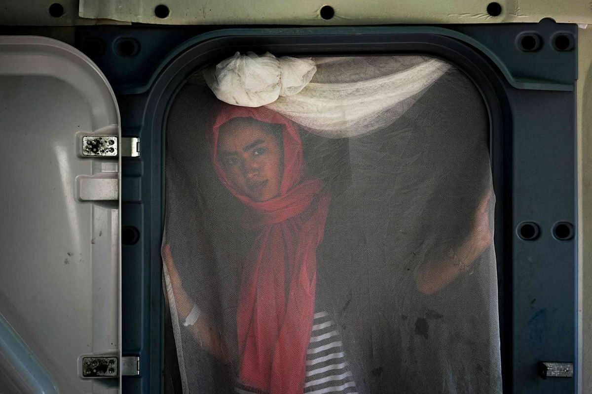 A woman from Afghanistan stands at the entrance to her prefabricated house at the Kara Tepe refugee camp on the island of Lesbos on October 6, 2016. PHOTO: AFP