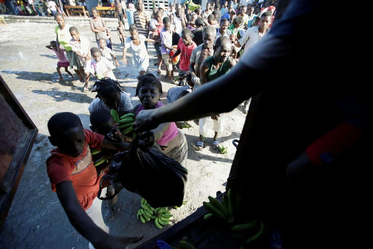 Residents at a shelter in the school Liliane Mars Dumarsais Estime fight for food during a delivery after Hurricane Matthew in Les Cayes, Haiti, on Oct 7.