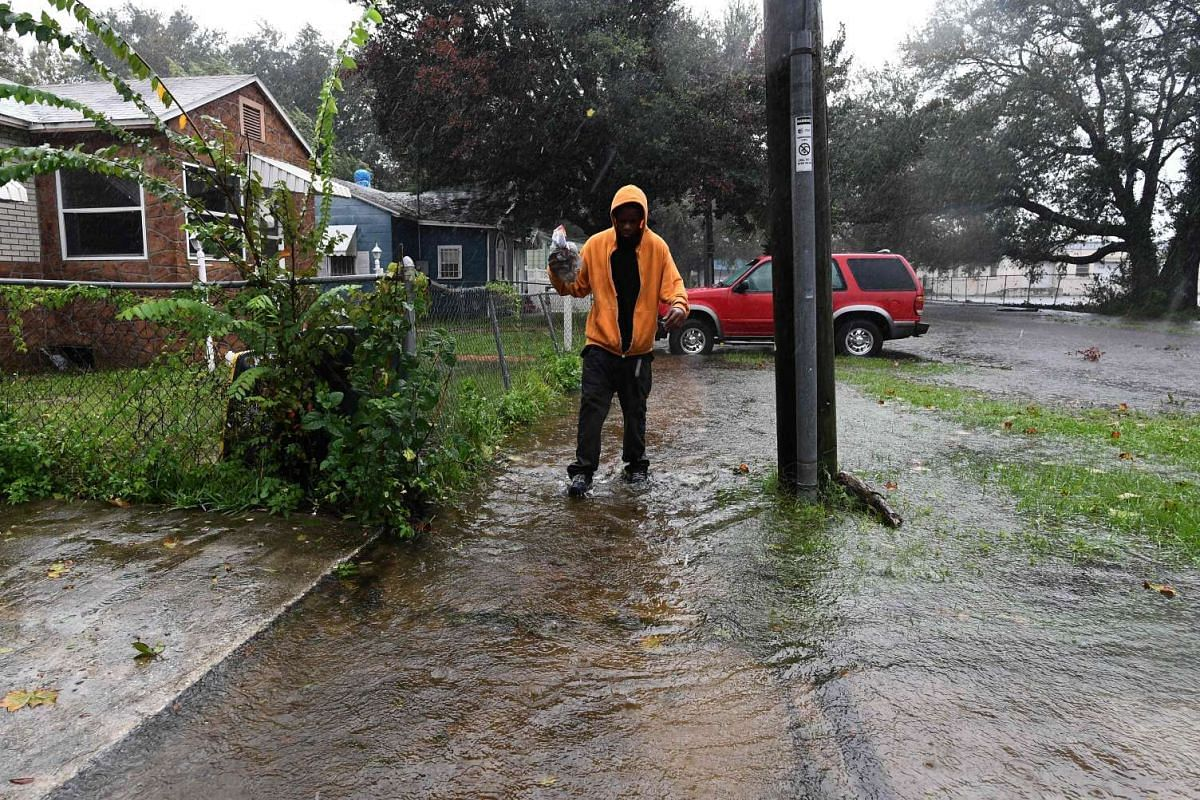 Alton Garvin, Jr., 23, wading through flood water near his mother's house in Jacksonville, Florida, on Oct 7,  as hurricane Matthew passes the area.