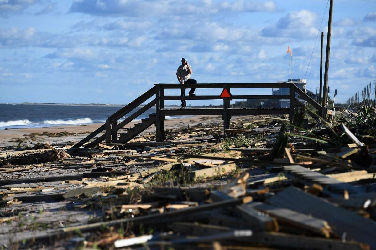 A man leans on a damaged boardwalk at a debris covered beach in St Augustine, Florida, on October 8, 2016, after Hurricane Matthew passed the area. PHOTO: AFP