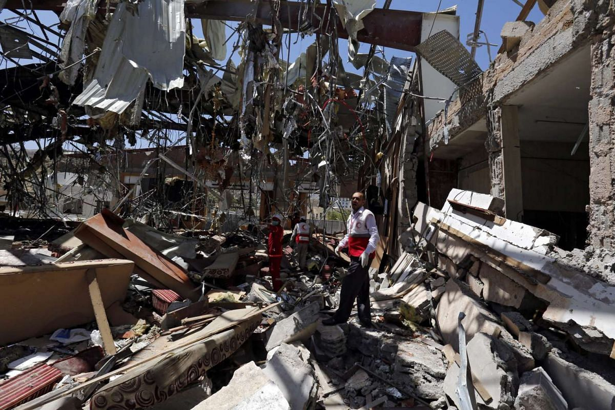 Members of Yemen Red Crescent Society look for remains of airstrikes victims inside the destroyed funeral hall a day after Saudi-led airstrikes targeted it, in Sana'a, Yemen, October 9,  2016.  PHOTO: EPA