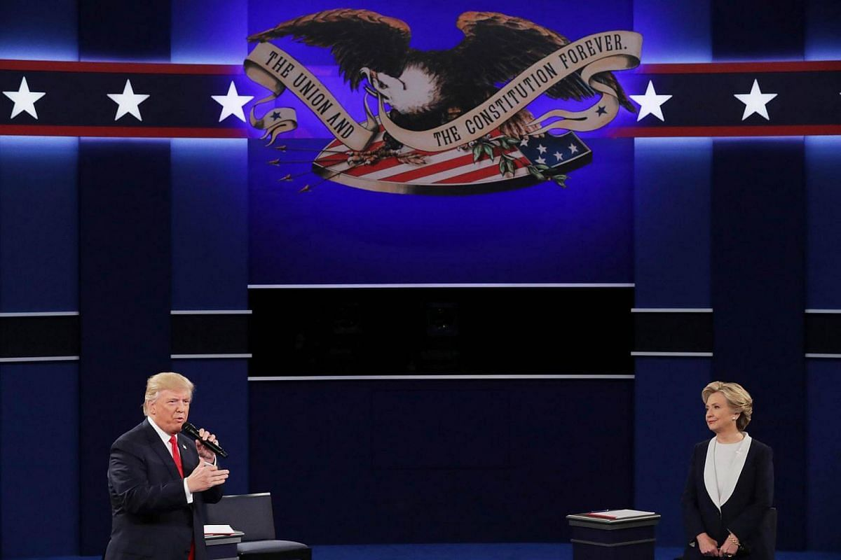 Republican presidential nominee Donald Trump (left) speaks as Democratic presidential nominee former Secretary of State Hillary Clinton looks on during the town hall debate at Washington University on Oct 9, 2016.