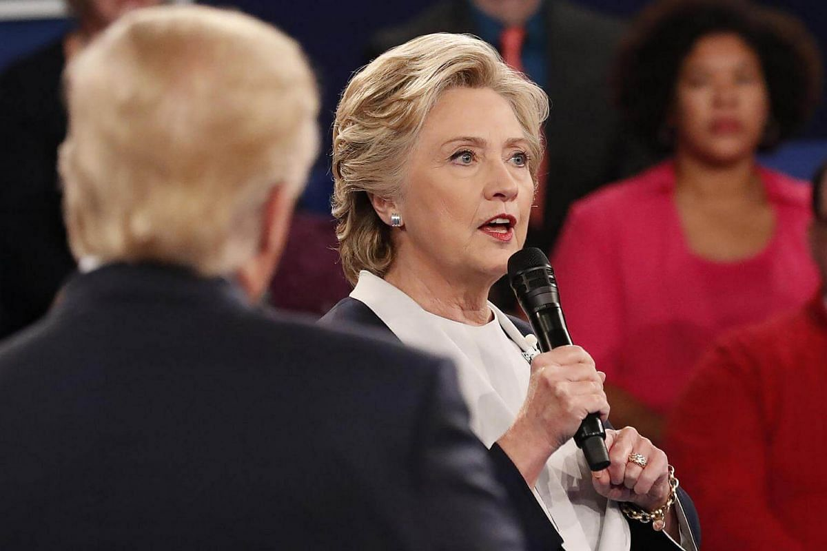 Democratic nominee Hillary Clinton (right) speaks as Republican nominee Donald Trump looks on during the second presidential debate at Washington University in St. Louis, Missouri on Oct 9, 2016.