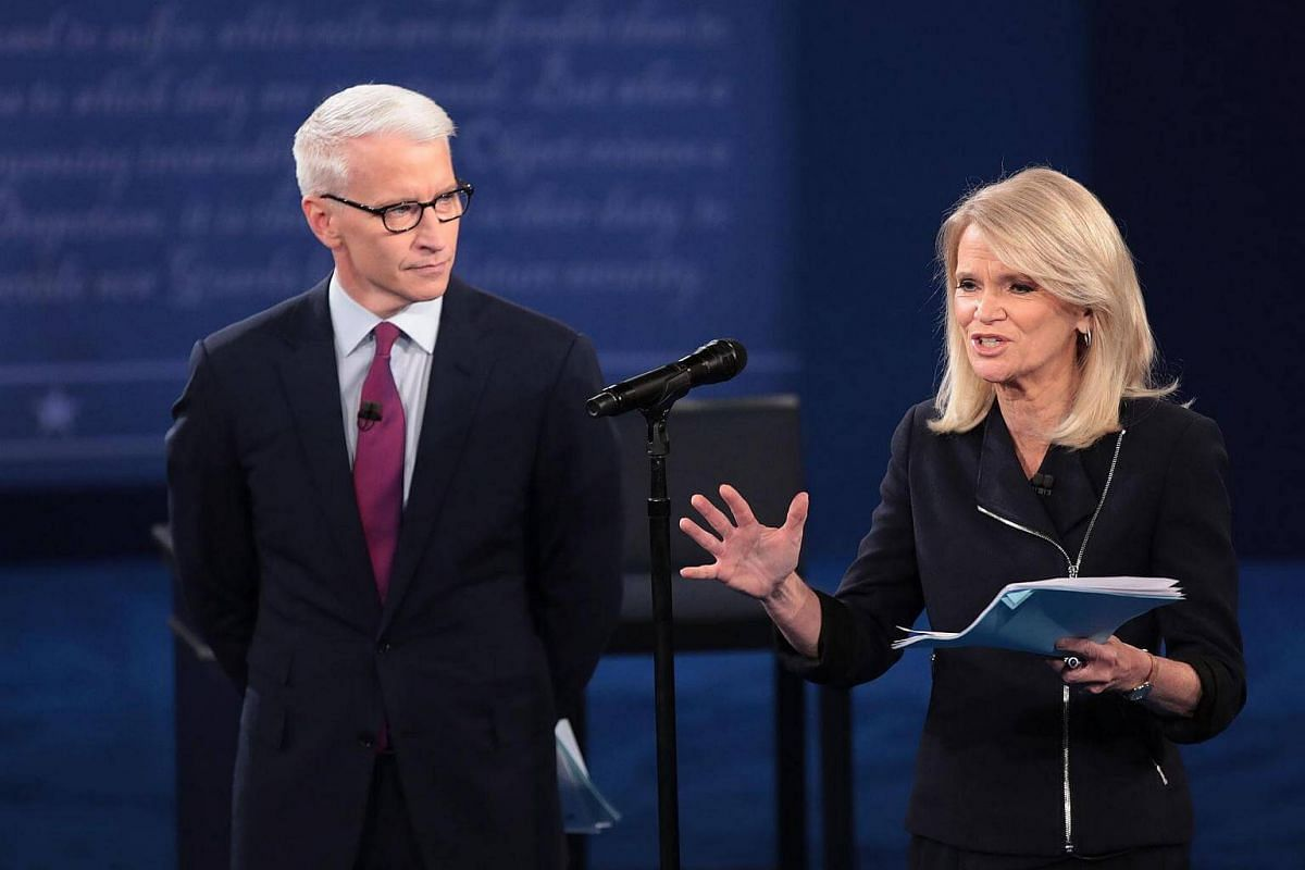 Moderator Anderson Cooper of CNN (left) and moderator Martha Raddatz of ABC speak before the town hall debate at Washington University on Oct9, 2016.
