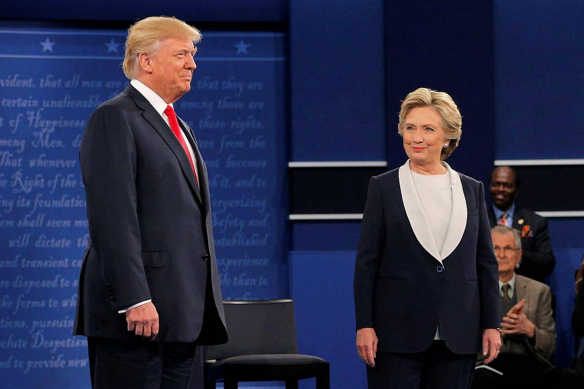 US Republican presidential nominee Donald Trump and US Democratic presidential nominee Hillary Clinton take the stage at their presidential town hall debate at Washington University in St. Louis, Missouri, US on Oct 9, 2016.