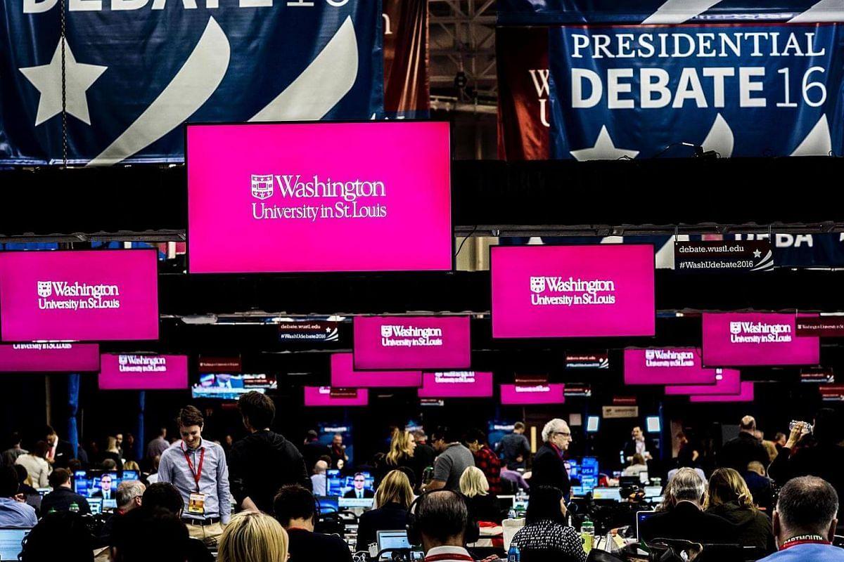 Before the start of Sunday night's debate, journalists work at the debate center at Washington University.