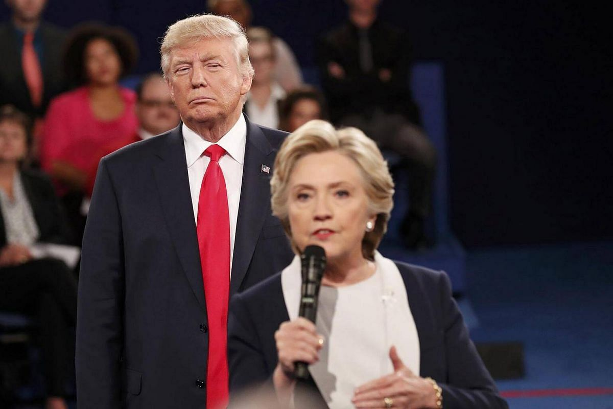 Republican US presidential nominee Donald Trump listens as Democratic nominee Hillary Clinton answers a question from the audience during their presidential town hall debate on Oct 9, 2016.