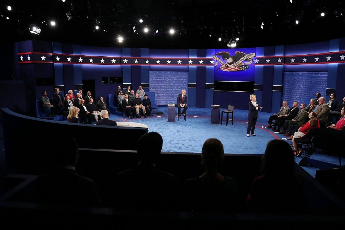 Republican Donald Trump (left) sits in his chair as Democrat Hillary Clinton (right) speaks during the second Presidential Debate at Washington University in St. Louis, Missouri, US, on Oct 9, 2016.
