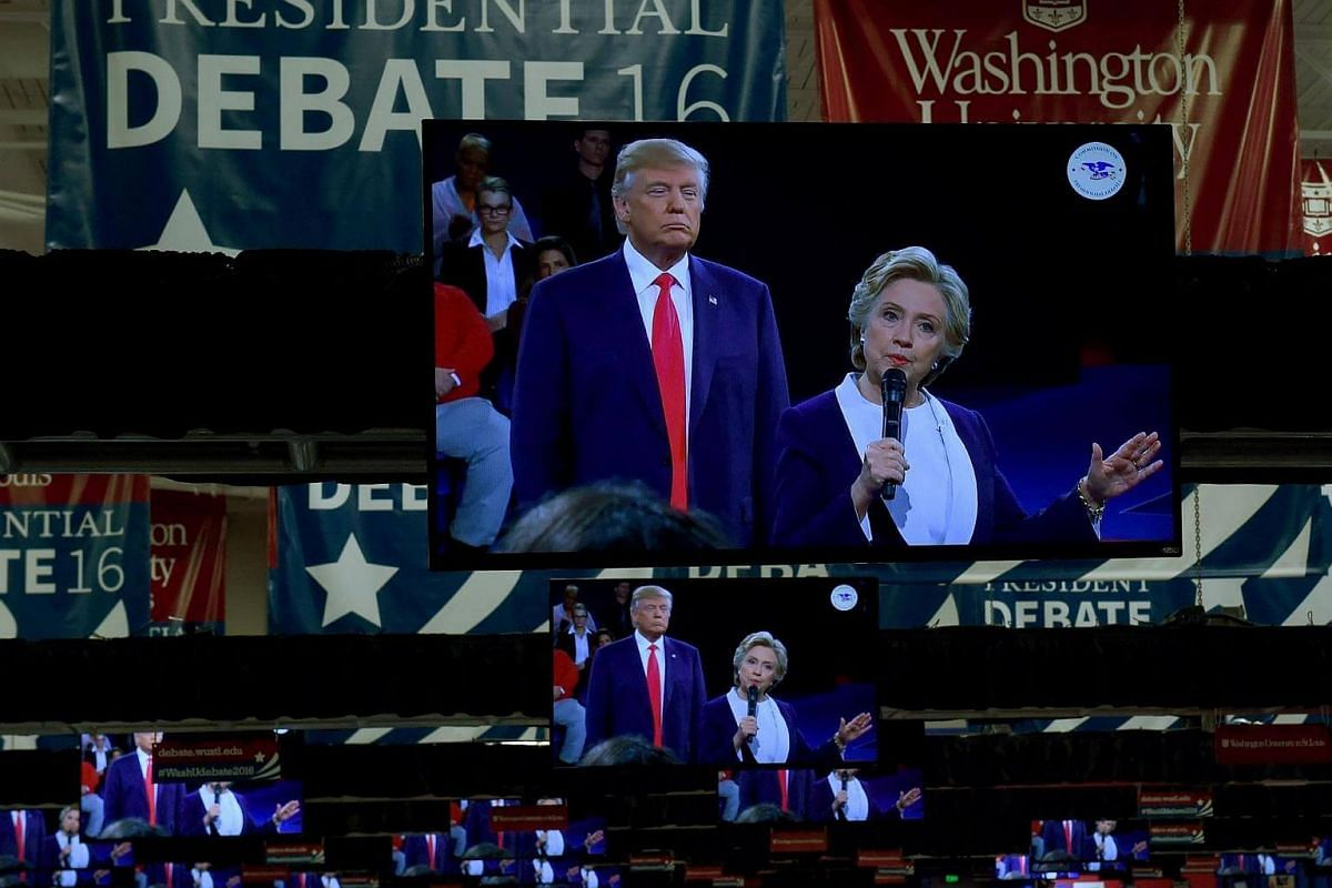 TV monitors in the press room show Republican nominee Donald Trump and Democrat nominee Hillary Clinton on stage as they participate in the 2nd debate at Washington University in St. Louis, Missouri on Oct 9, 2016.