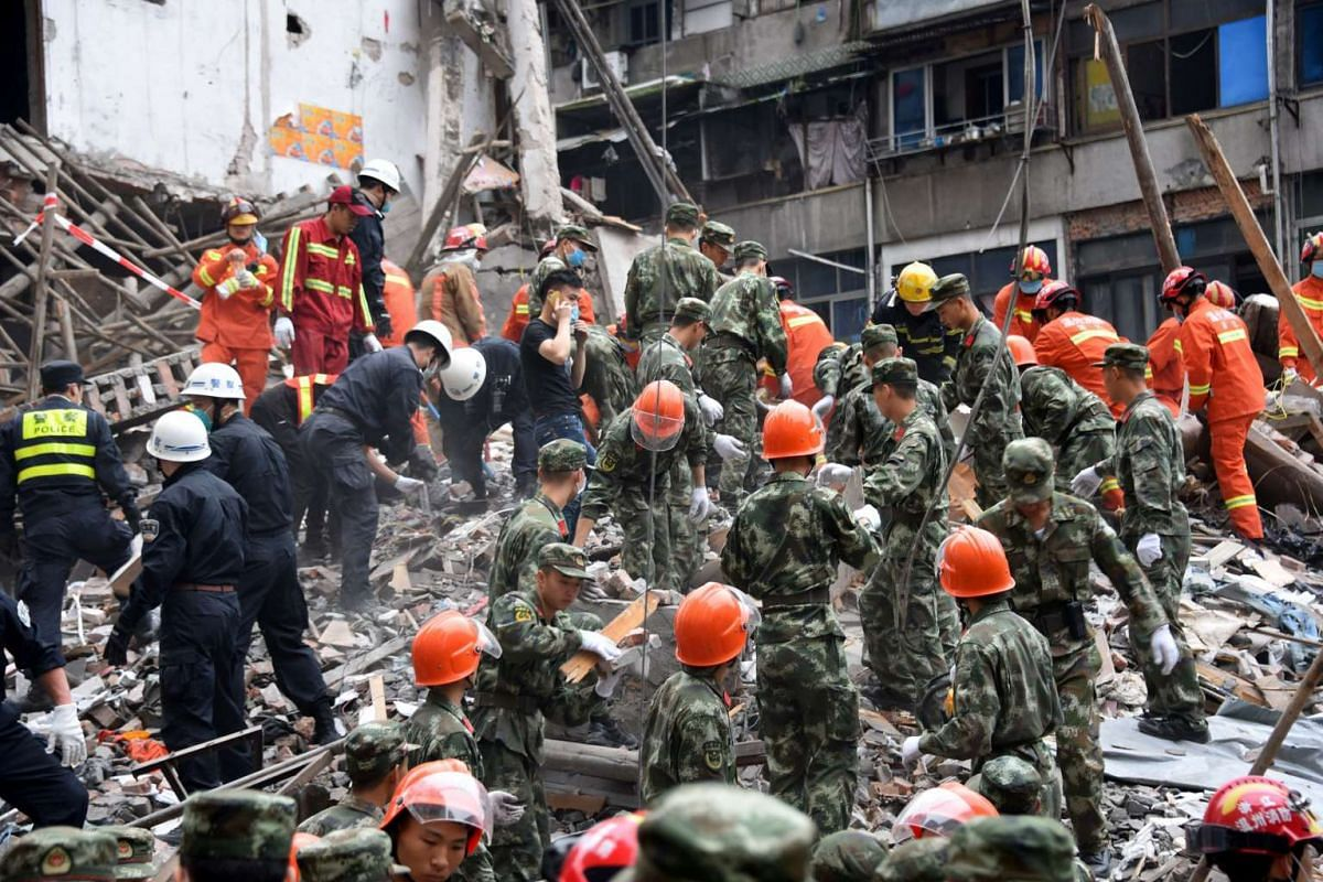 Rescuers search for survivors after four buildings caved in during the early hours in Wenzhou, eastern China's Zhejiang province, killing at least 17 people, on Oct 10, 2016.