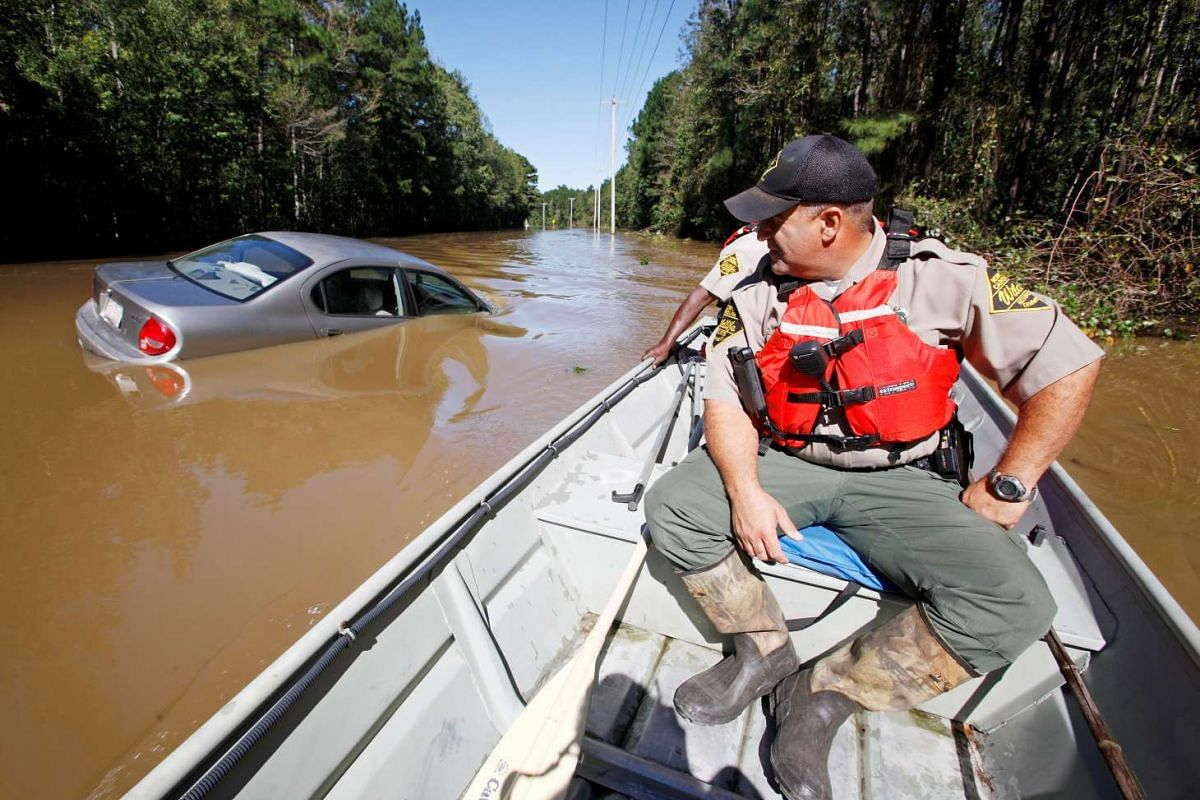 North Carolina Wildlife Resources Commission officers search a submerged road for those in need of rescue as river waters rise dangerously after Hurricane Matthew hit Lumberton on Oct 10, 2016.