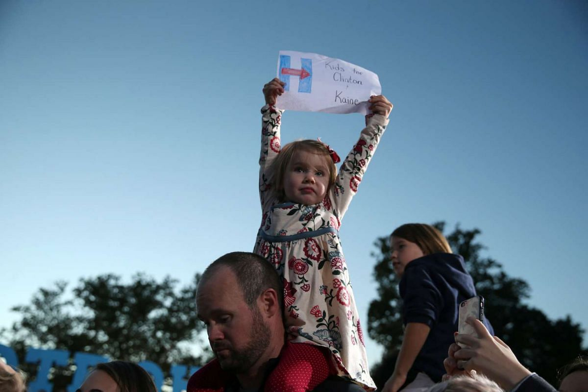 Michael Pierce, 35, holds his three-year-old daughter Evelyn as they listen to U.S. Democratic presidential nominee Hillary Clinton speak at a rally at Ohio State University in Columbus, Ohio, U.S. October 10, 2016. PHOTO: REUTERS