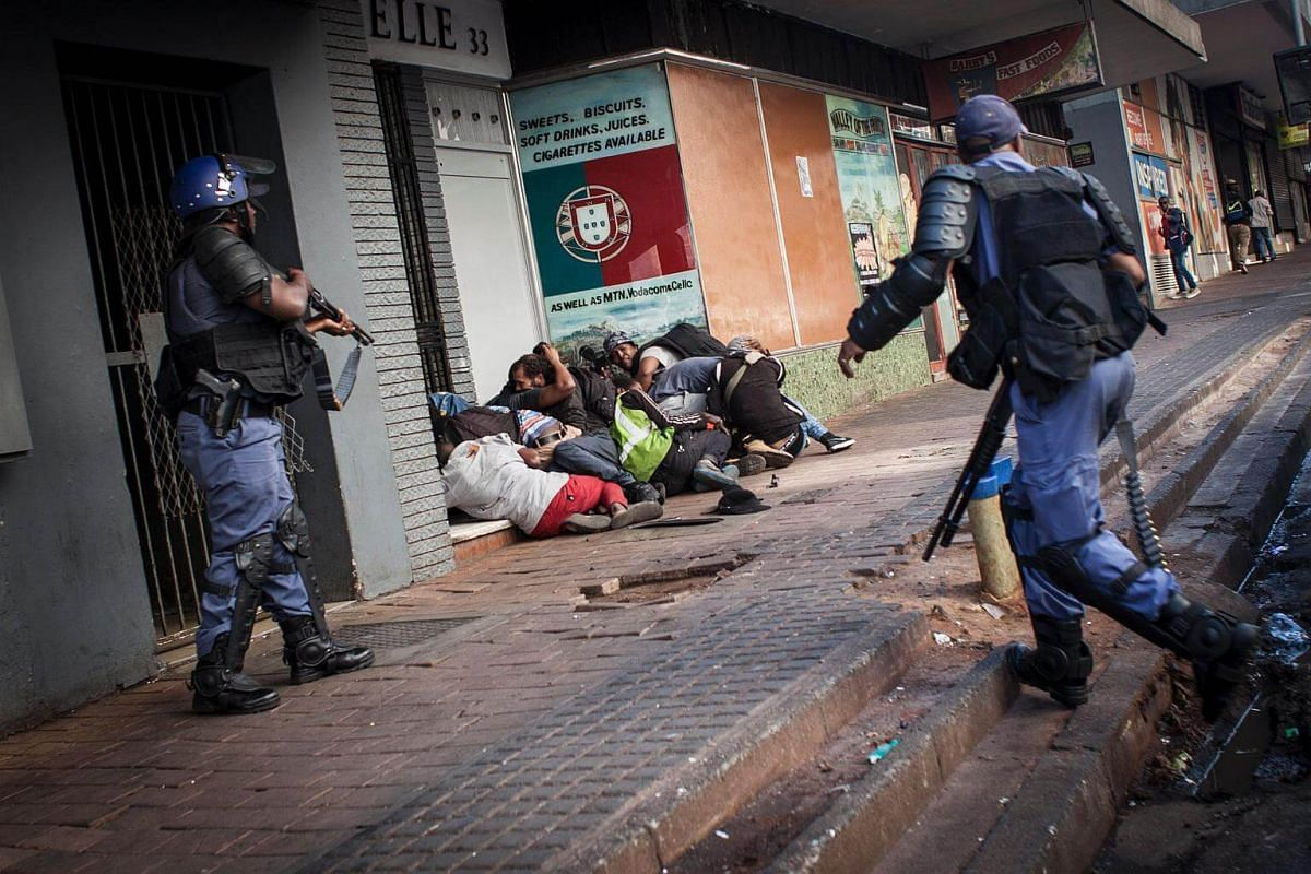 A riot policeman points at protesters after the FeesMustFall protest spills onto the streets in the Braamfontein district, in Johannesburg.