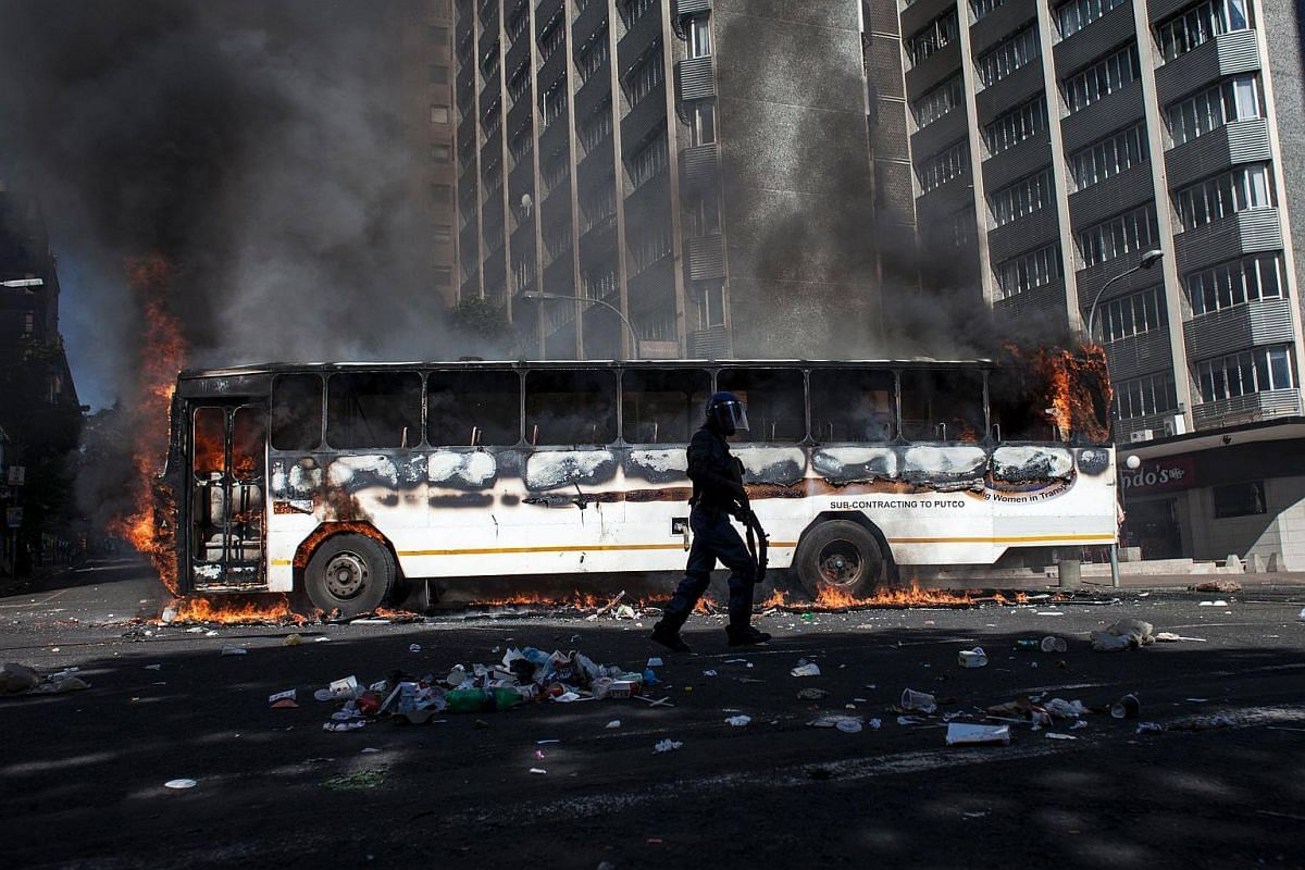 A policeman runs in front of a bus that was set alight after the FeesMustFall protest spills onto the streets of the Braamfontein district in Johannesburg.