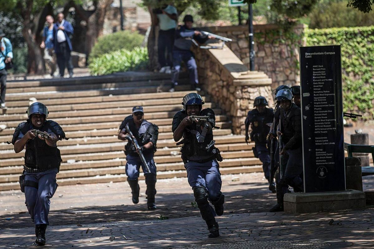 South African anti riot policemen fire rubber bullets during running battles at the Witwatersrand University in Johannesburg.