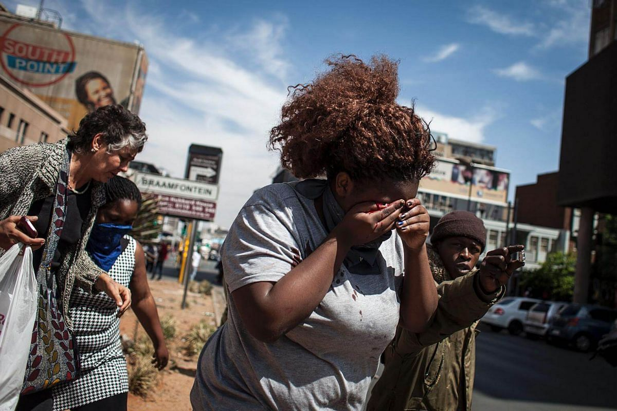 A protester is hit in the face by a rubber bullet as the FeesMustFall protest spills onto the streets of the Braamfontein in Johannesburg.