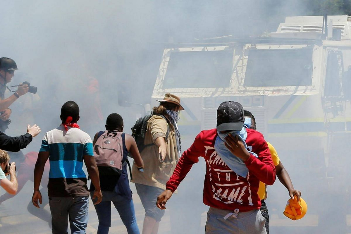 Demonstrators run away from a police vehicle during student protests demanding free education at the Witwatersrand University, in Johannesburg, South Africa.