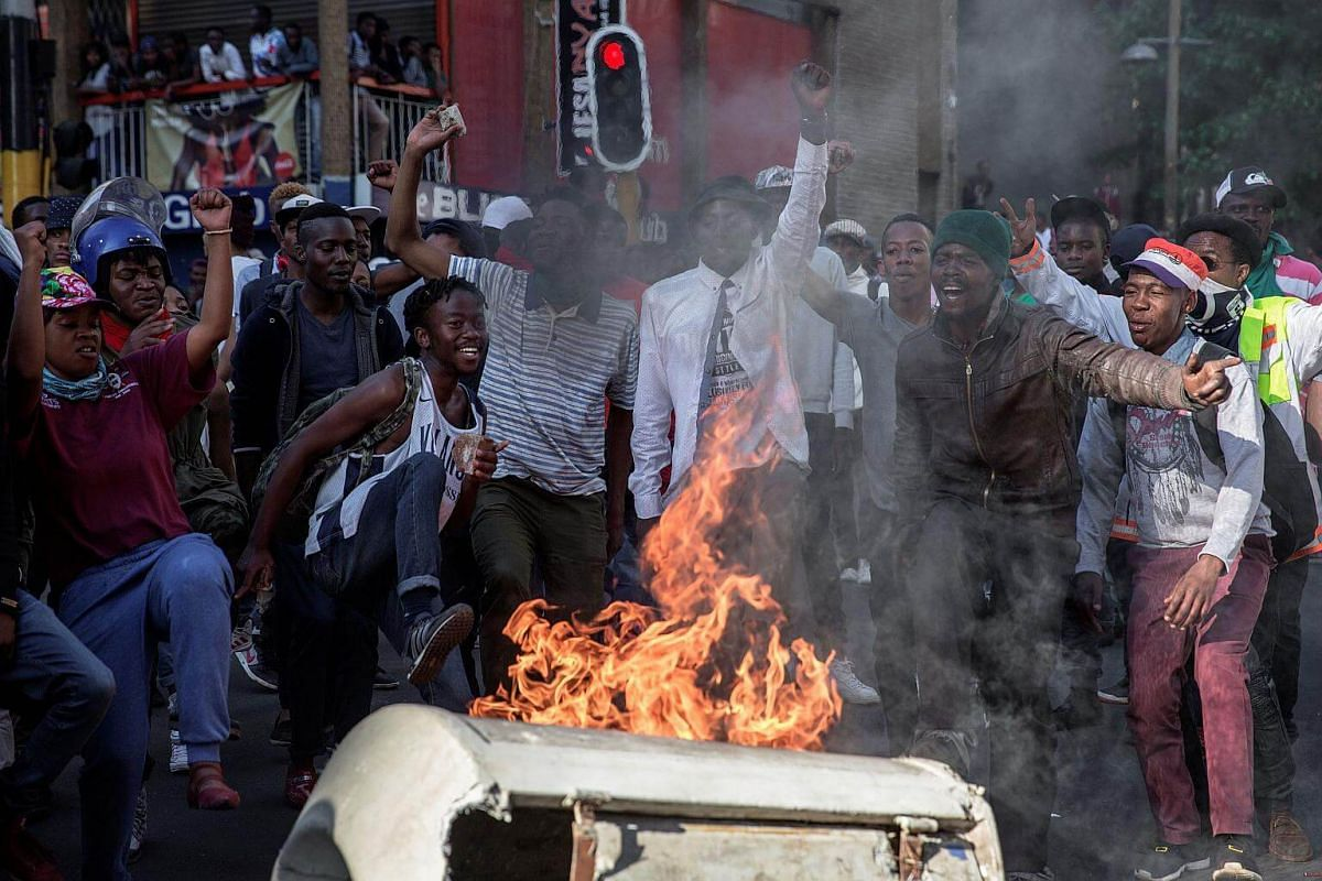 People gesture and chant slogans during clashes between student and police forces in Johannesburg.