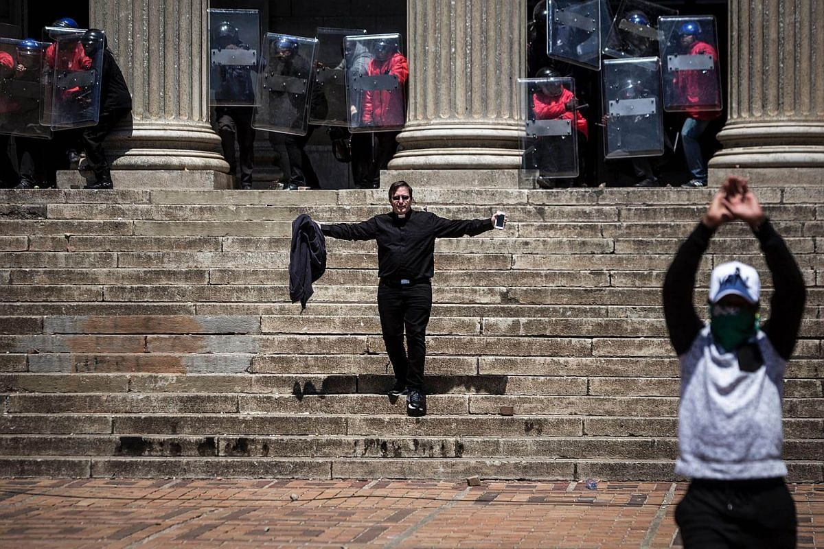 A priest gestures as he walks down the stairs while South African anti-riot police officers protect themselves with shields.