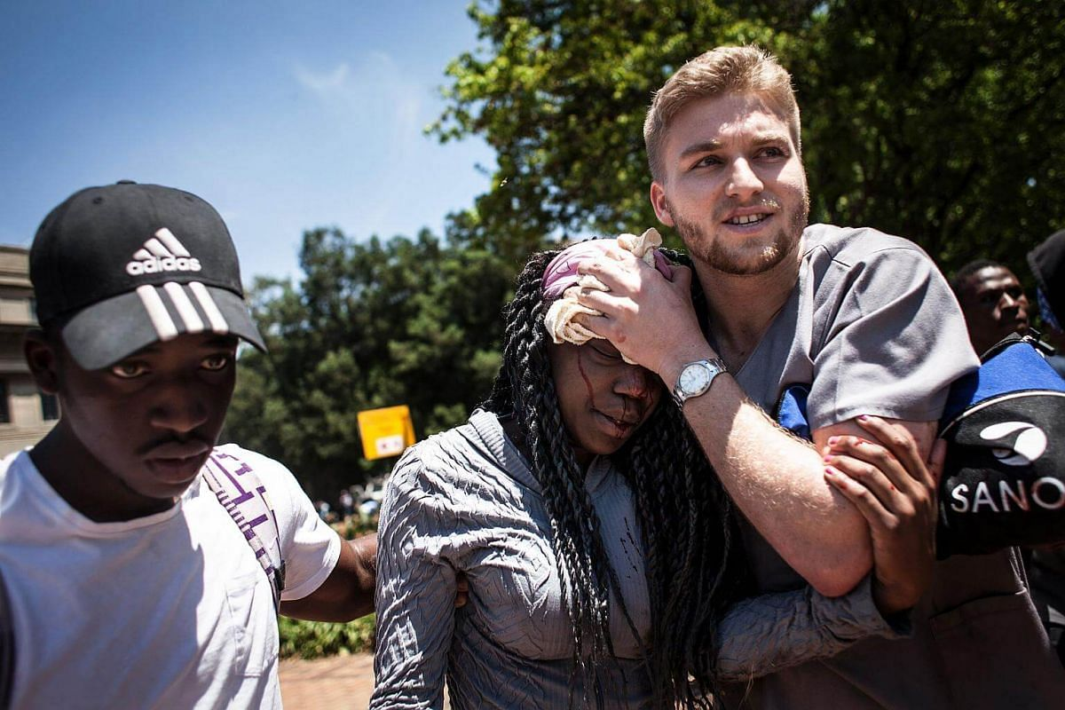 A man covers the head of an injured woman during clashes between students and police forces in Johannesburg.