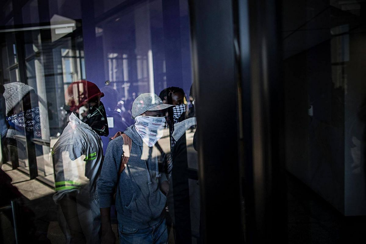 Masked students enter a building of the Witwatersrand University in Johannesburg to disrupt classes in a bid to shut down the campus.