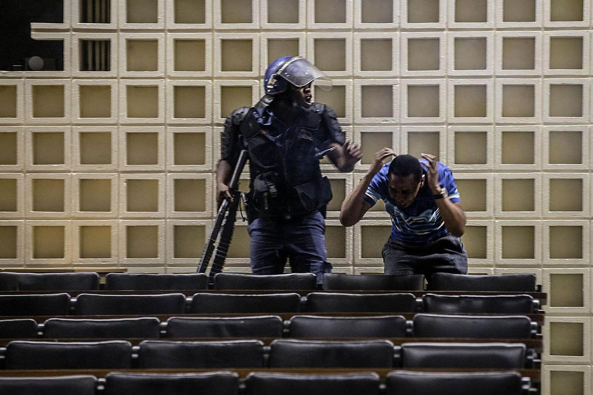 A South African anti-riot policeman reacts after masked students enter a building of the Witwatersrand University in Johannesburg.