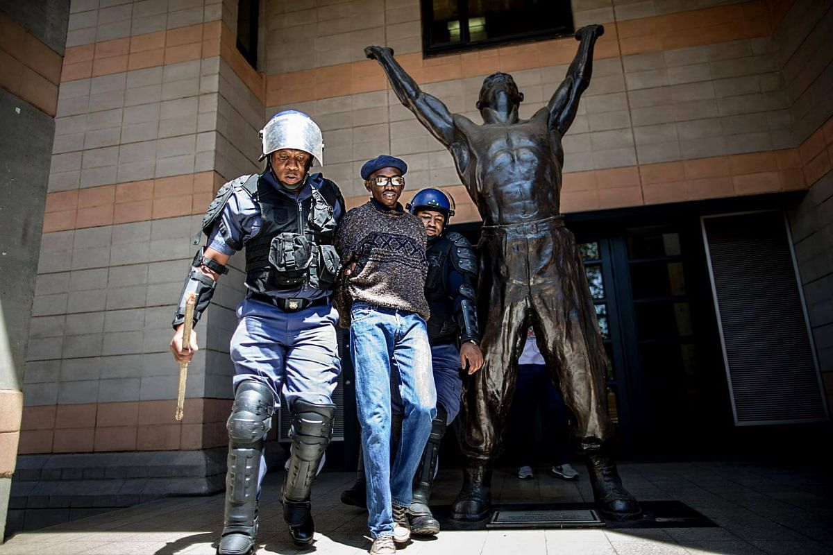 A student is detained by a South African anti-riot policeman after he entered a building of the Witwatersrand University in Johannesburg.