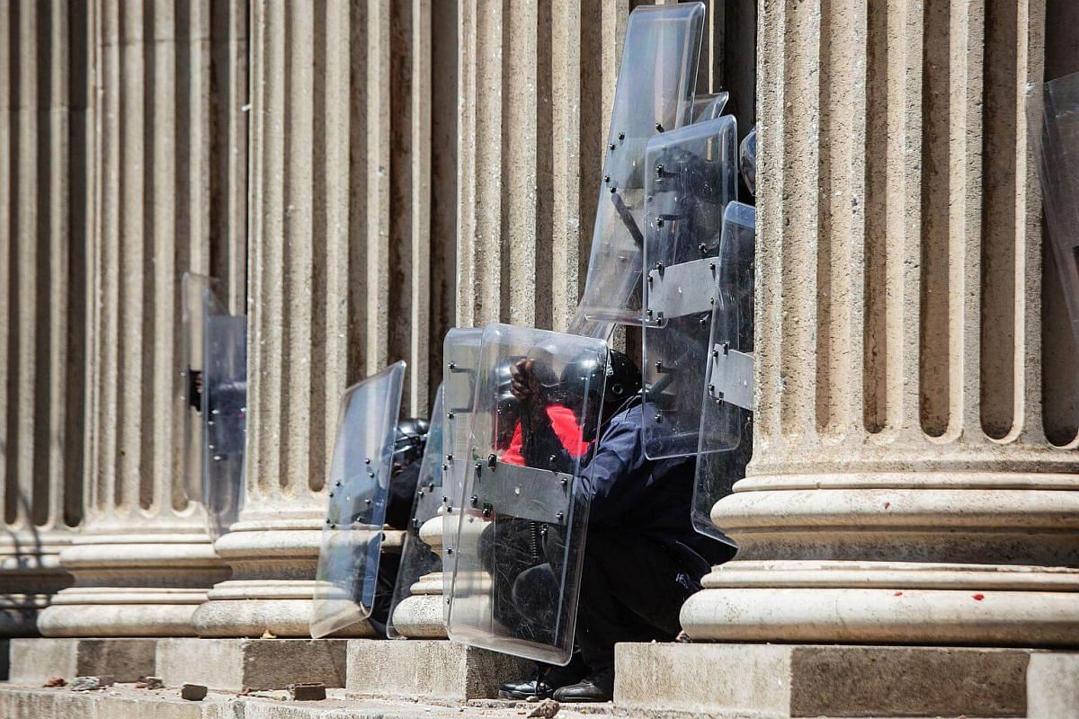University private security members protect themselves from stones thrown by students from the University of Witwatersrand.