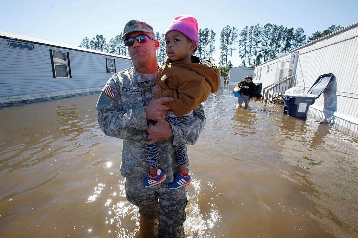 National Guard Sergeant Jeremy Stellhorn carries two-year-old Cathalawa Olivia through flood waters as they rescue residents of a mobile home park inundated by rising river waters after Hurricane Matthew hit the state, in Lumberton, North Carolina, o