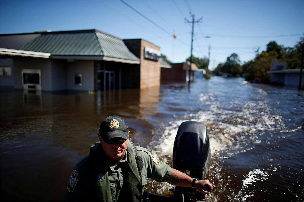 South Carolina Department of Natural Resources officer Dwayne Rodgers surveys the flooded downtown area caused by Hurricane Matthew.