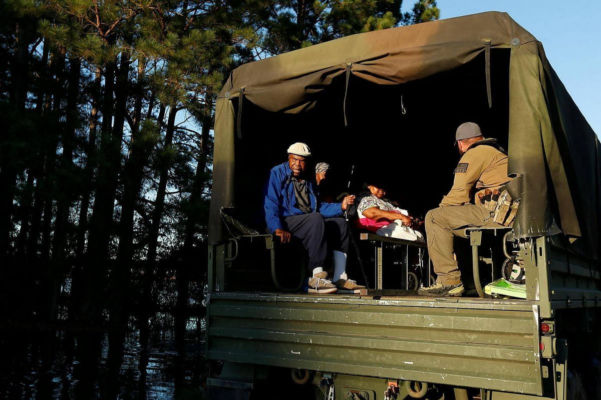 Evacuees sit in a rescue truck in a flood area caused by Hurricane Matthew in Lumberton, North Carolina, on Oct 10, 2016.