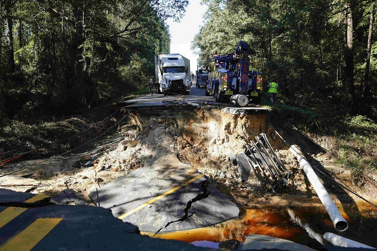 A semi truck that drove past a barricade is removed from a washed away road on Highway 117 as flood waters in the wake of Hurricane Matthew continue to rise in Goldsboro, North Carolina, on Oct 10, 2016.